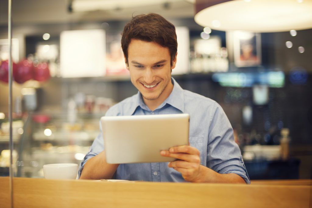 Smiling man using digital tablet in cafe